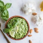 easy basil pesto recipe with ingredients scattered around a bowl.